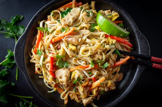 pad Thai on black dish with lime garnish
