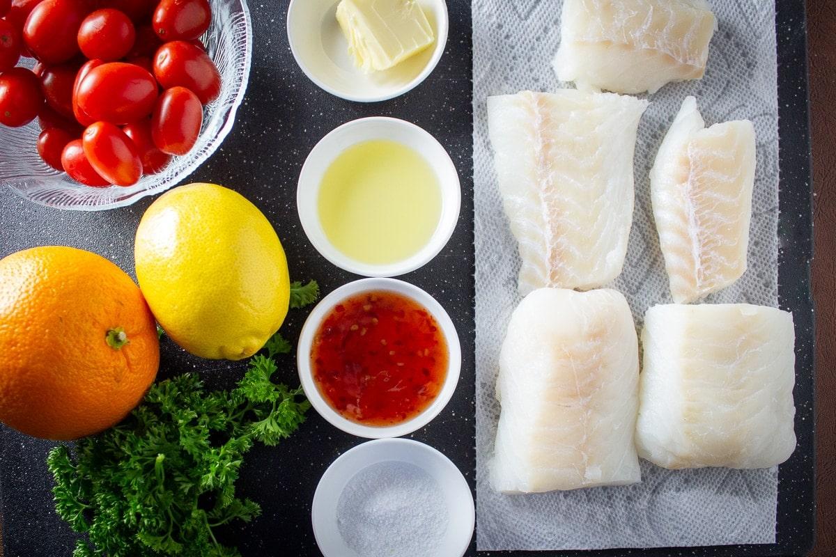 cod fillet pieces, butter, oil, Thai sweet chili sauce, salt, parsley, lemon, orange, cherry tomatoes