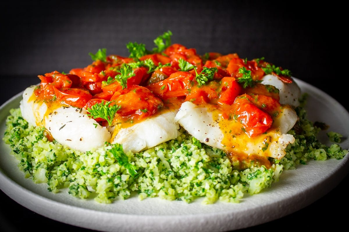baked cod fillets covered with cherry tomato sauce over cauliflower spinach rice