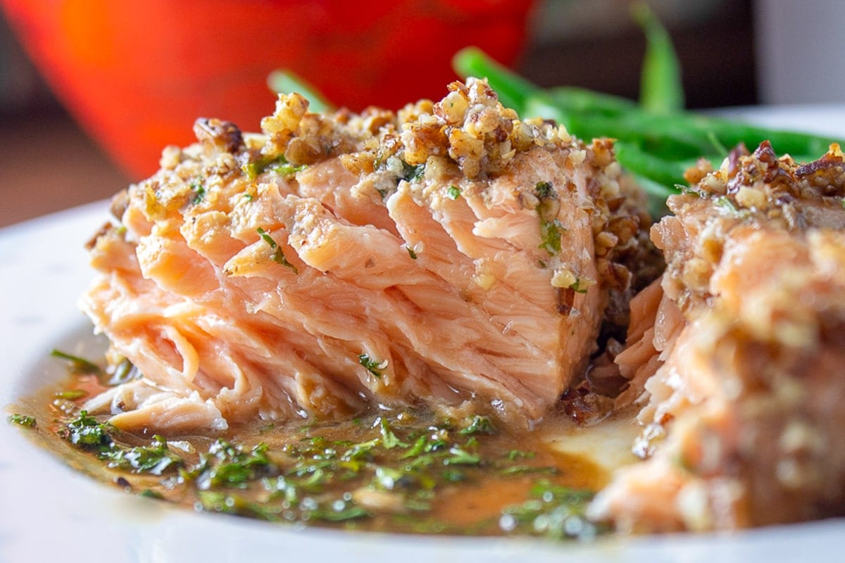 inside piece of pecan crusted salmon on plate with beans