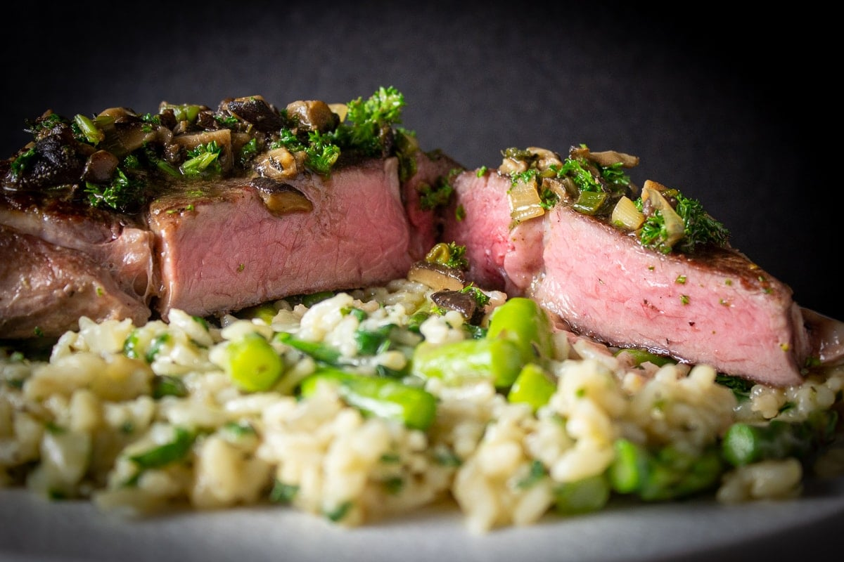 sous vide veal chops over risotto on plate