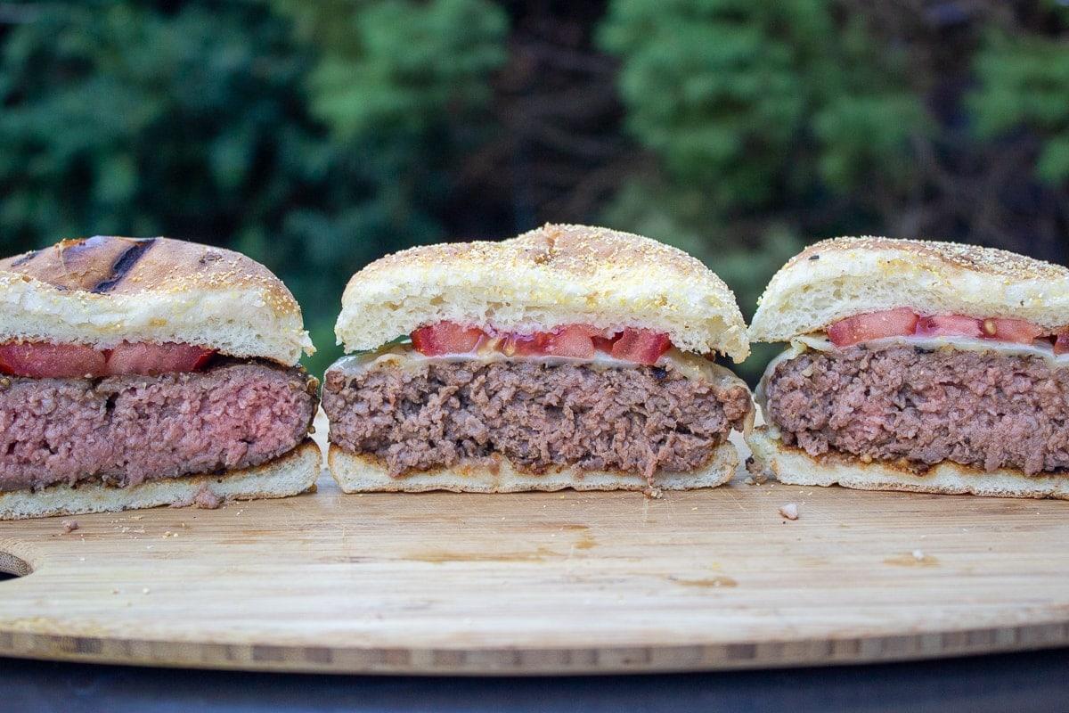 3 half burgers in buns on cutting board