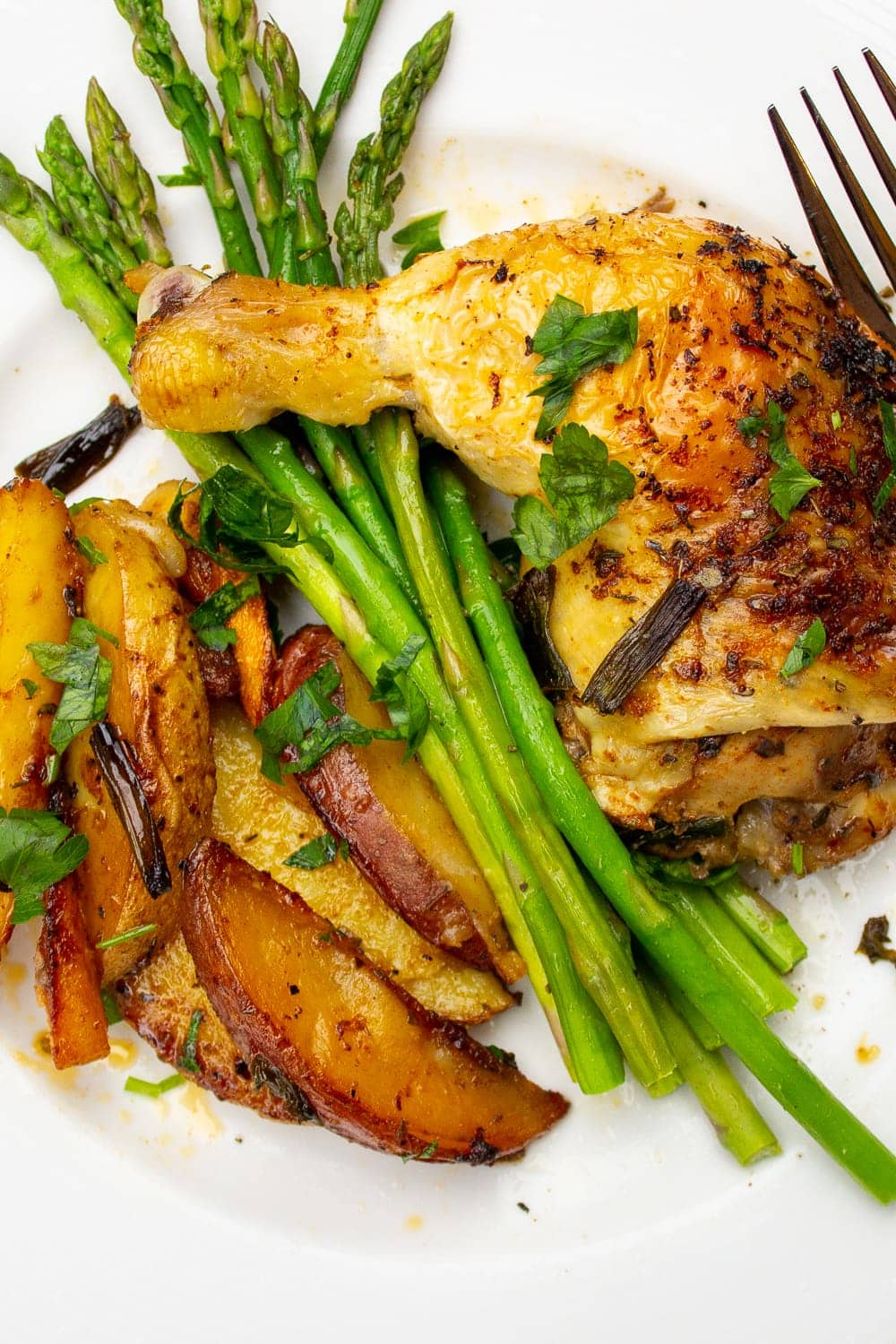 chicken quarter leg with asparagus and potatoes on plate p