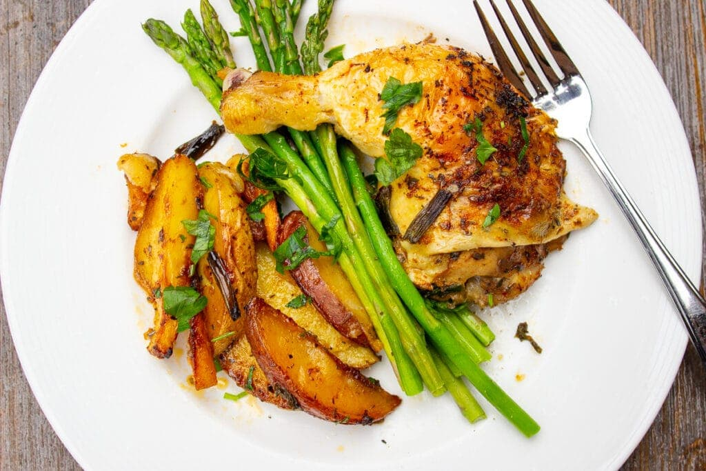 chicken quarter leg with asparagus and potatoes on plate