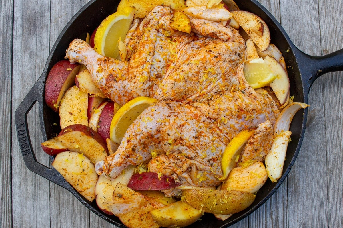 uncooked chicken, potatoes and lemon in skillet