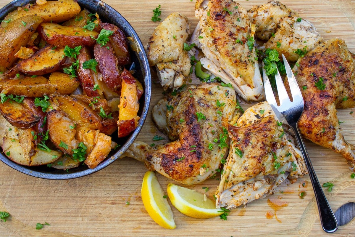 cut up chicken on cutting board with bowl of potatoes