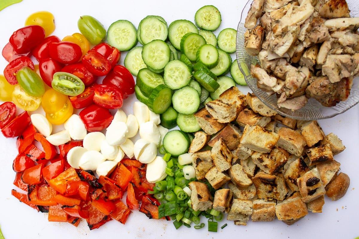 chopped salad ingredients, bread, chicken on cutting board