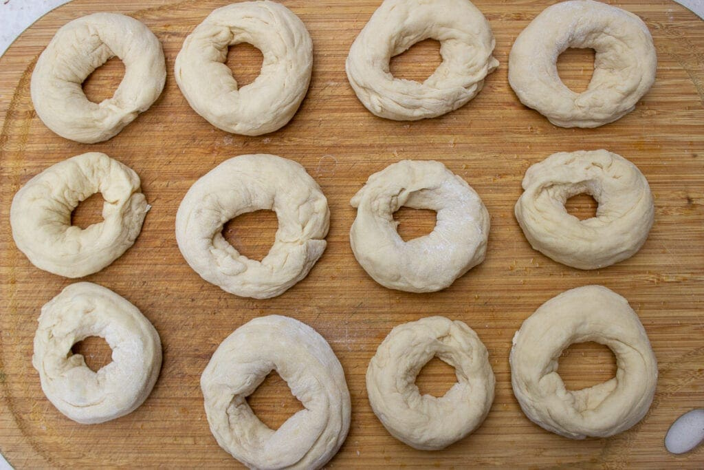 dough shaped into bagels on cutting board