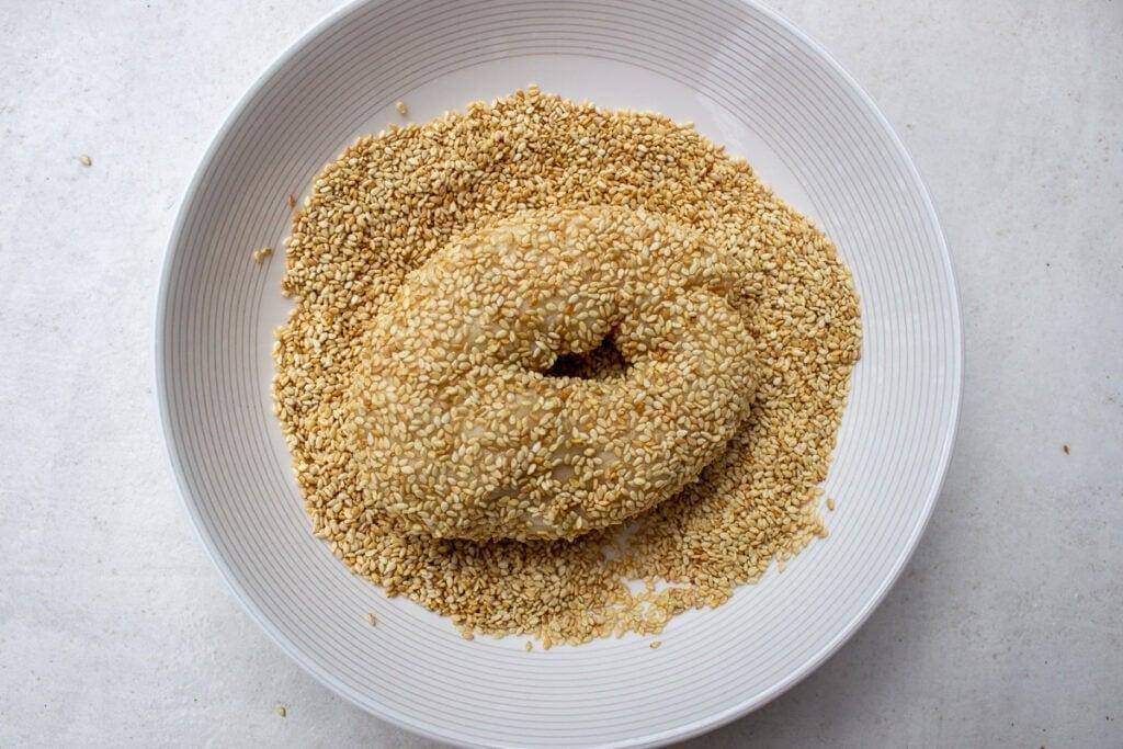 boiled bagels dipped in sesame seeds in bowl