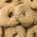 sesame seed bagels piled on cutting board p