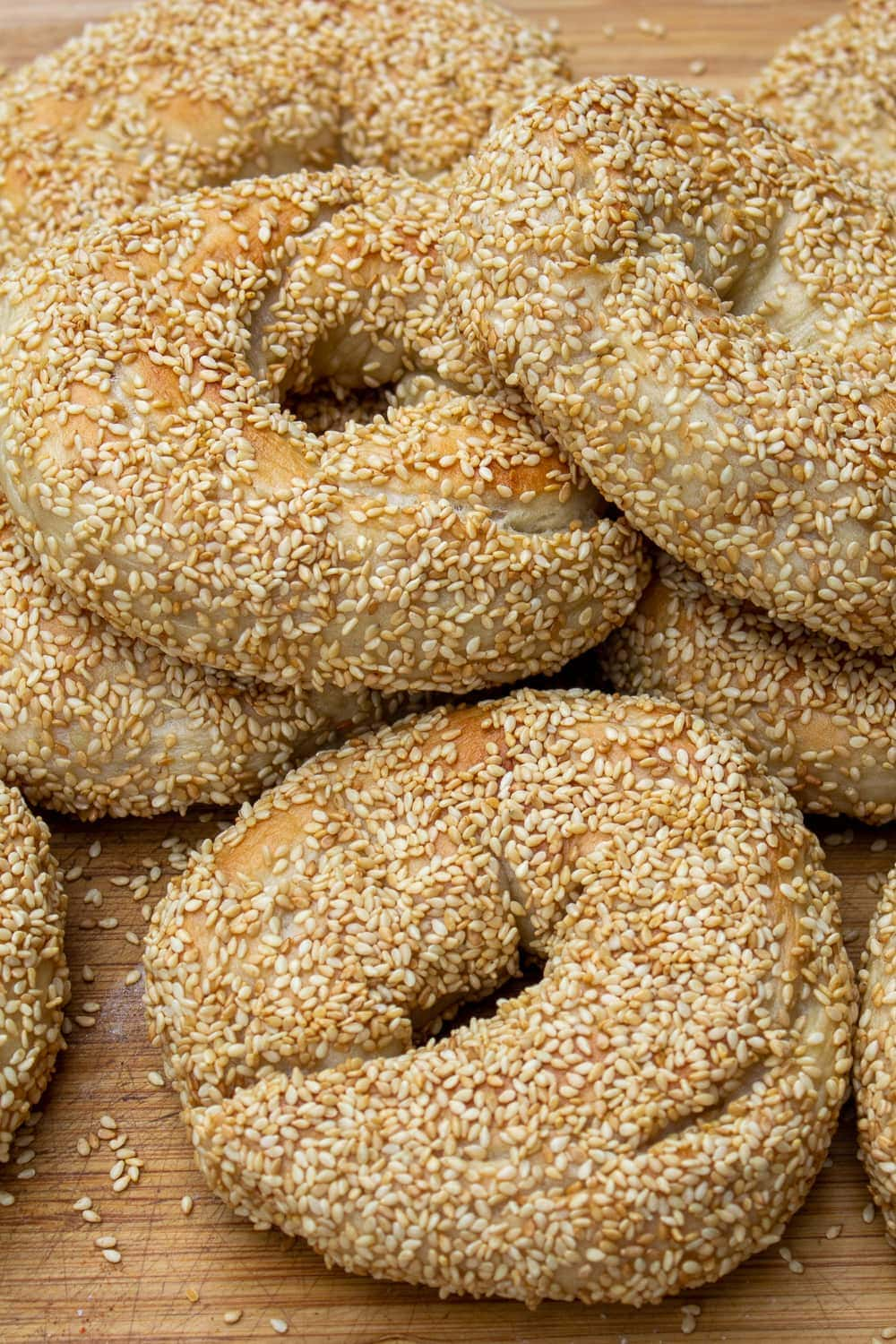 sesame seed bagels piled on cutting board p1