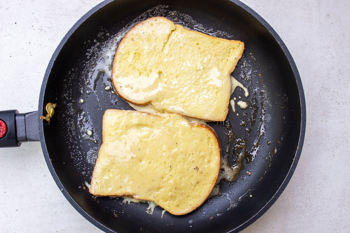 2 slices of french toast in pan showing uncooked side