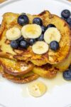stack of banana French toast on plate with berries and banana slices p1