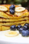 stack of banana French toast cut in half on plate with berries and banana slices p2