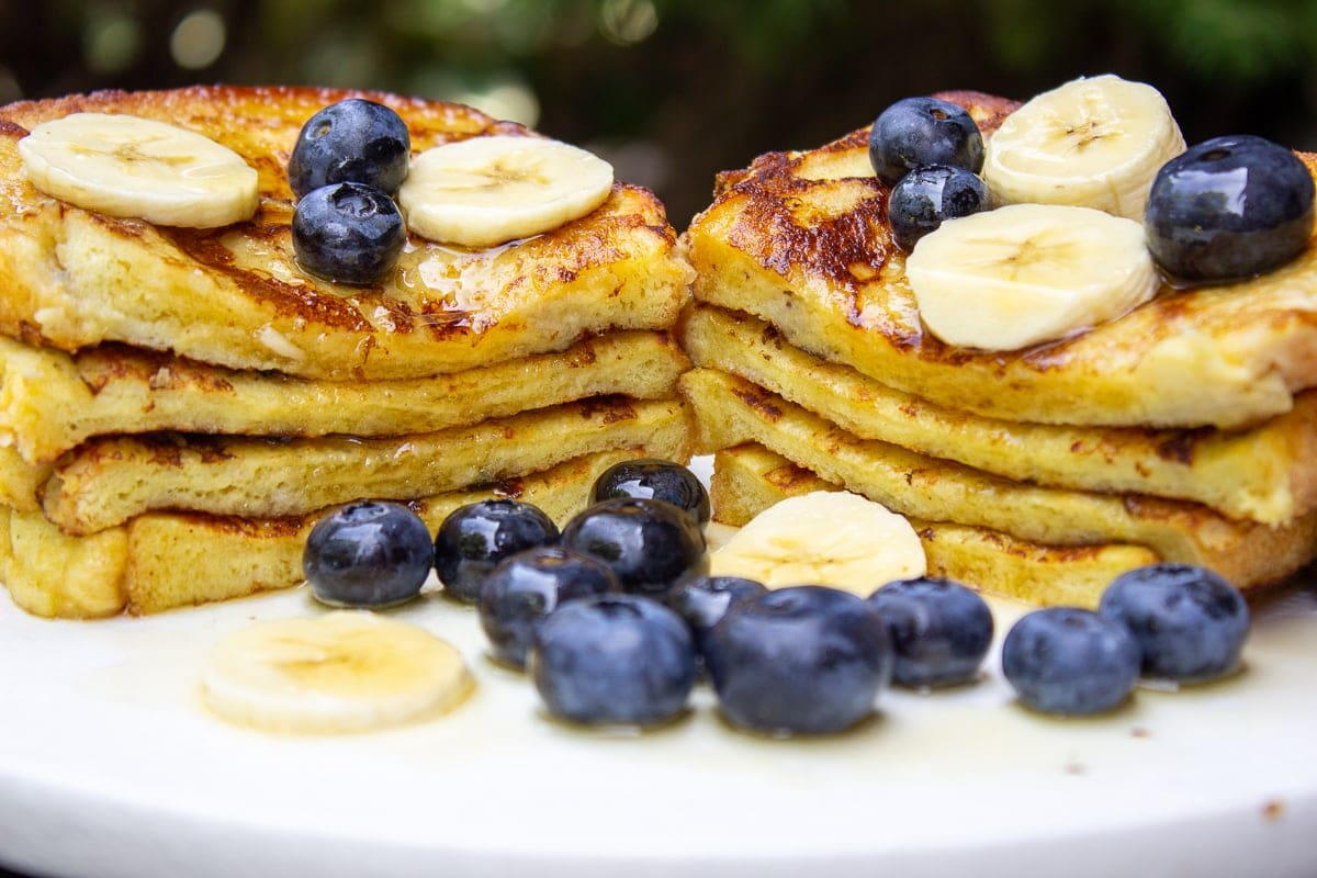 stack of banana French toast cut in half on plate with berries and banana slices