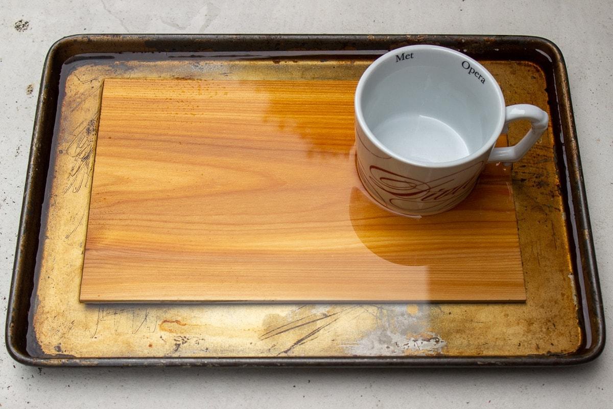 plank soaking in water in a tray