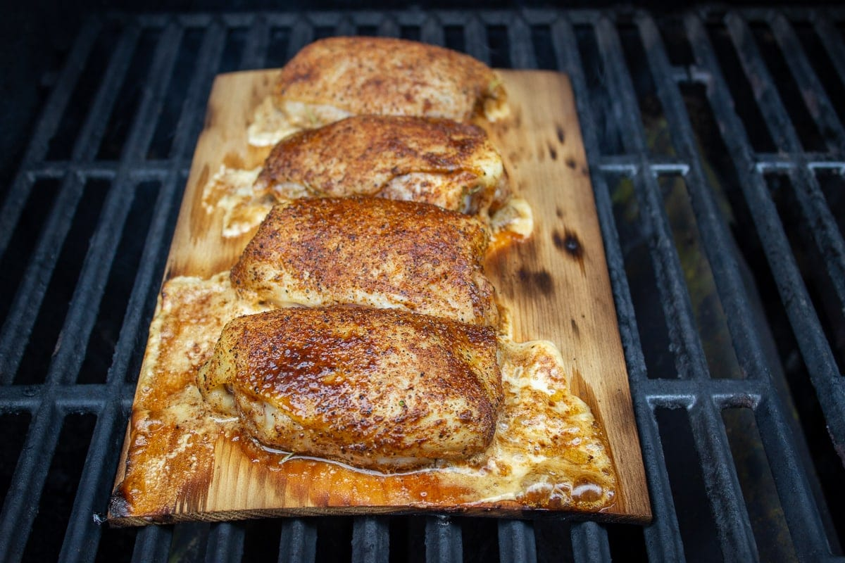 chicken thighs on plank on grill