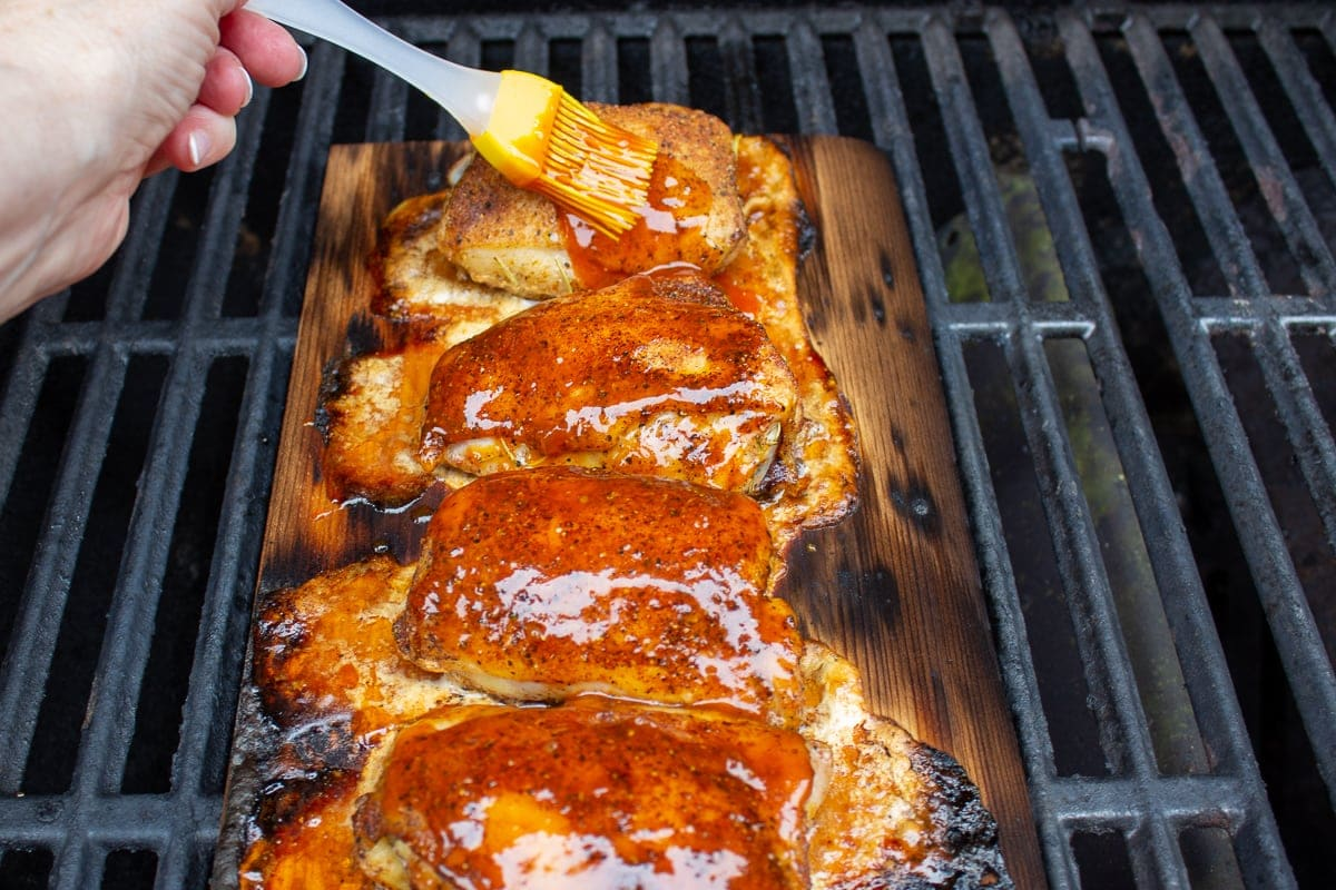 chicken thighs on plank on grill with sauce