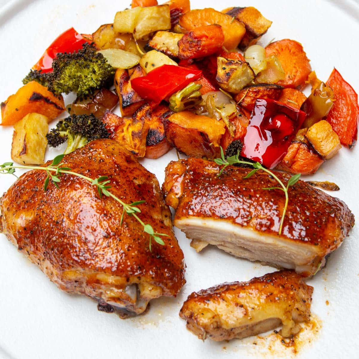 cooked chicken thighs on plate with vegetables