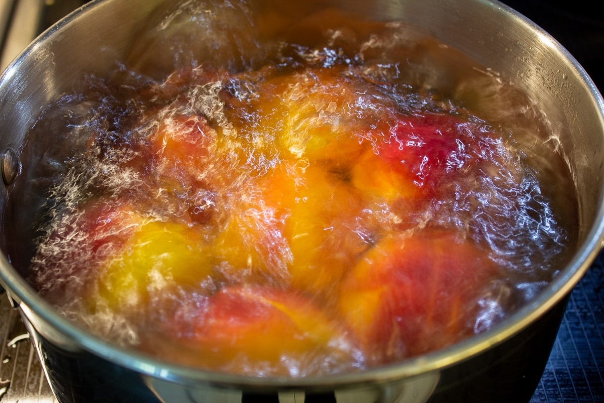 peaches boiling in pot of water