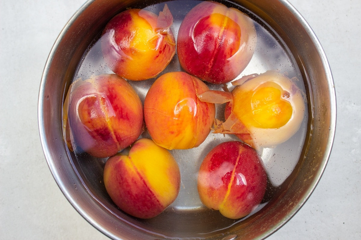 peaches floating in cold water in pot