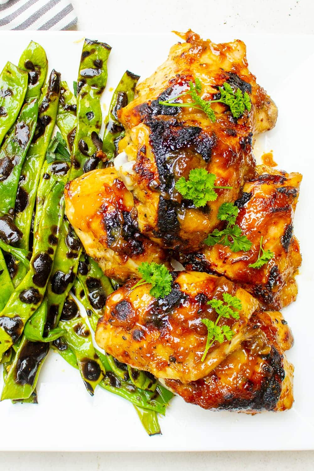 glazed chicken thighs with green beans on plate p2