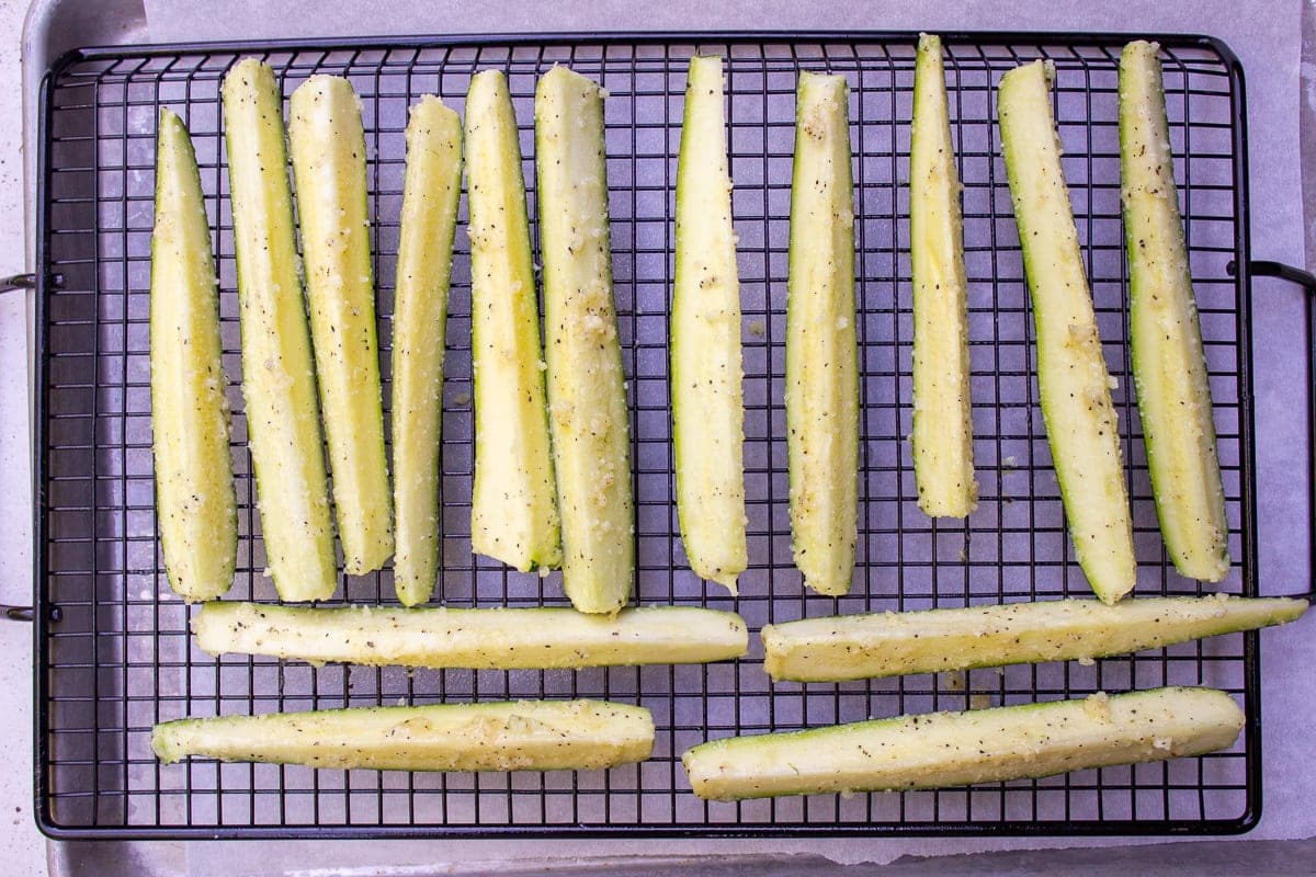 coated zucchini spears on oven rack on pan