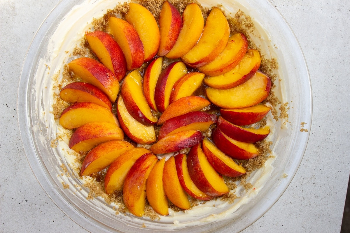 peaches fanned out over sugar in pie plate