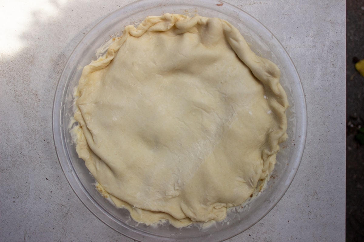 dough covering peaches in pie plate