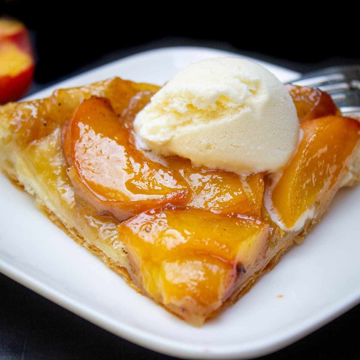 piece of peach tarte with ice cream on plate