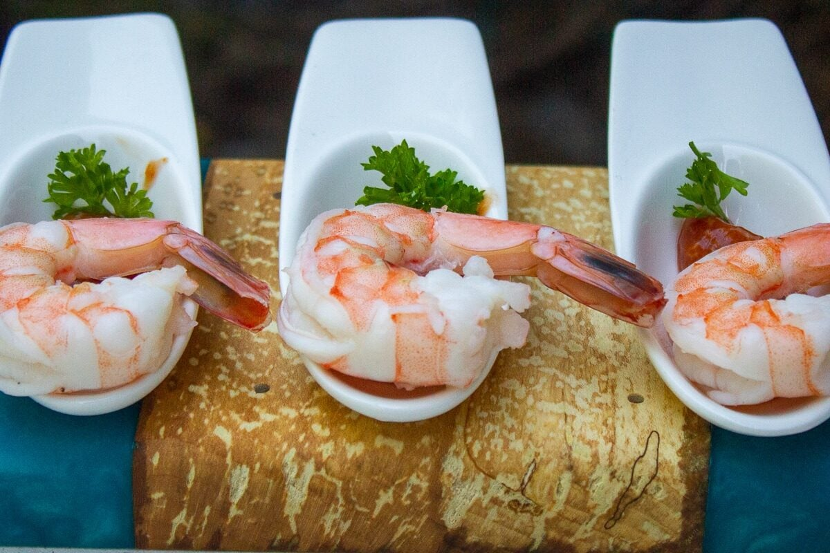 individual shrimp on spoons with sauce