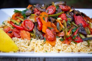 Roasted Veggies on top of Spiced Rice on a plate