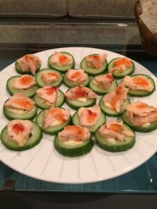 Salmon on cucumber rounds topped with spicy thai sauce